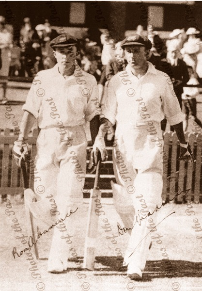 Ron Hamence and Don Bradman, walking to bat. (with signatures) c1940s