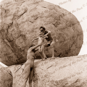 Aborigine family climbing rock, Devils Marbles, near Tennant Creek NT. c1936. Northern Territory