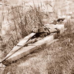 How to shoot ducks, shooter's canoe with trigger cord in his mouth, Victoria, c1934. Title 'How to shoot a crocodile!'