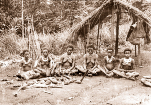 Six Papuan women & girls sitting on ground with yams. Papua New Guinea
