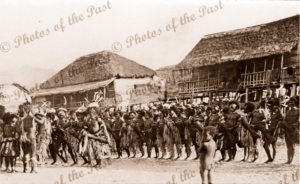 European group at native village. Probably Hanuabada. Papua New Guinea. 1916