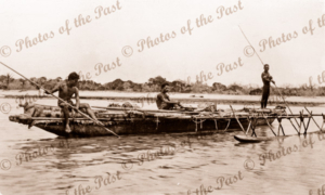 A large native out-rigger canoe. Three young men on board. Papua New Guinea. 1916