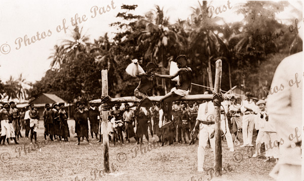 A pillow fight. Two boys fight it out at Samarai, Papua New Guinea. Red Cross Day. 1916